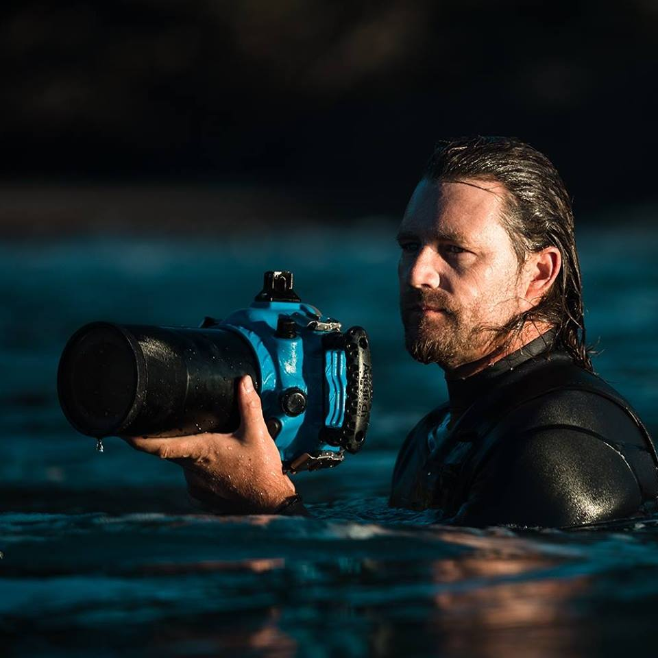 Photographer Warren Keelan in the ocean with camera